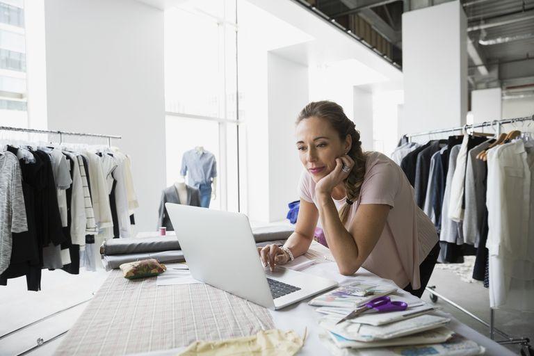Fashion designer with sewing patterns using laptop