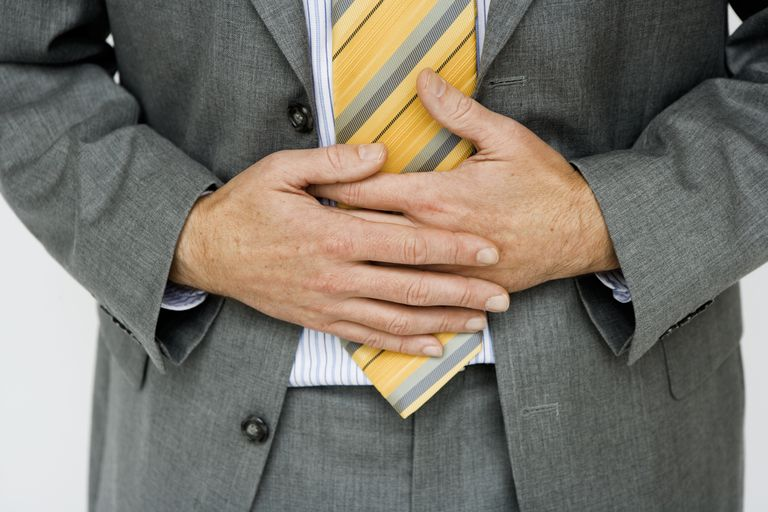 man in suit holding stomach