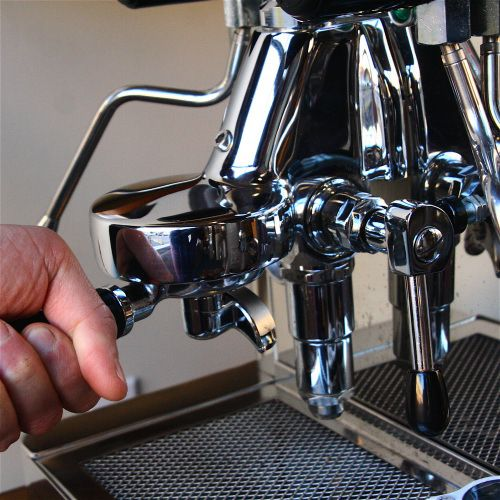A barista firmly locking the portafilter into the group head.