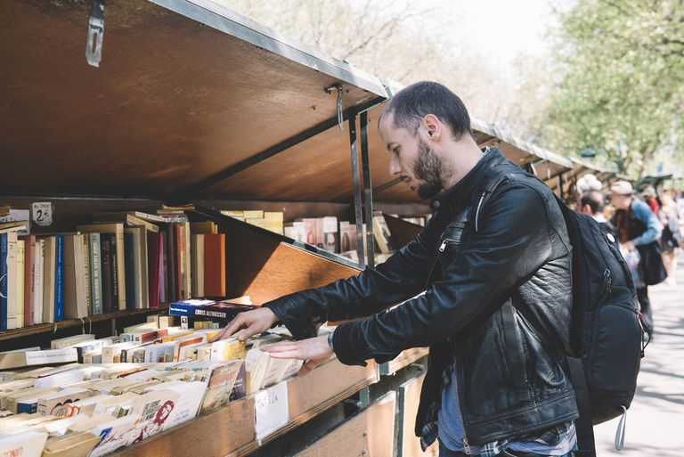 France, Paris, man looking for old books in the Bouquinistes of Paris along the banks of the Seine