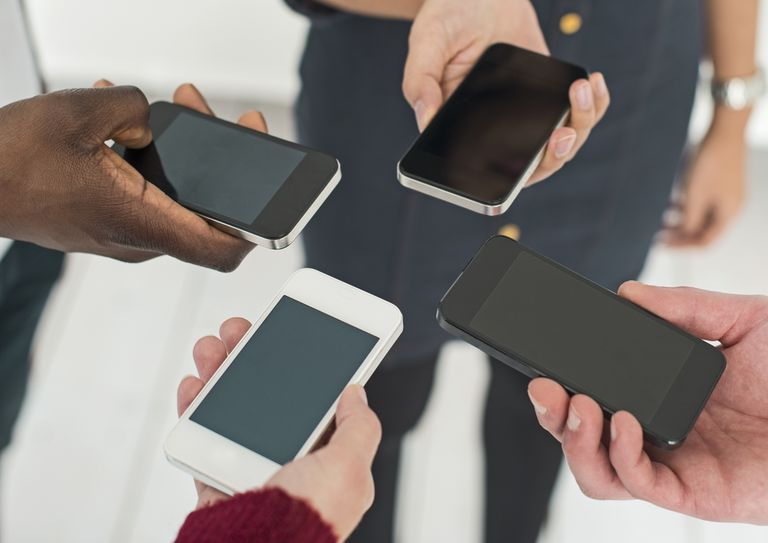 Four people with smartphones exchanging data