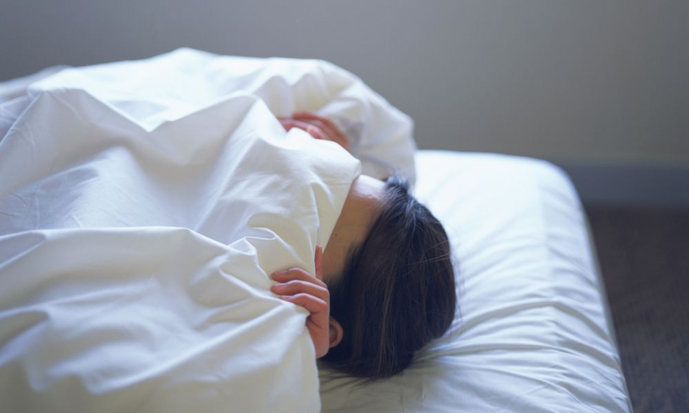 Woman lying in bed covering face with sheet
