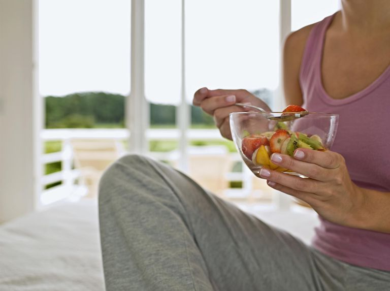 Woman sitting on bed, holding fruit salad, mid section