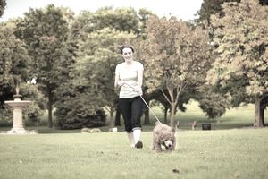 Young Woman Walking with Pet Puppy Poodle in Nature