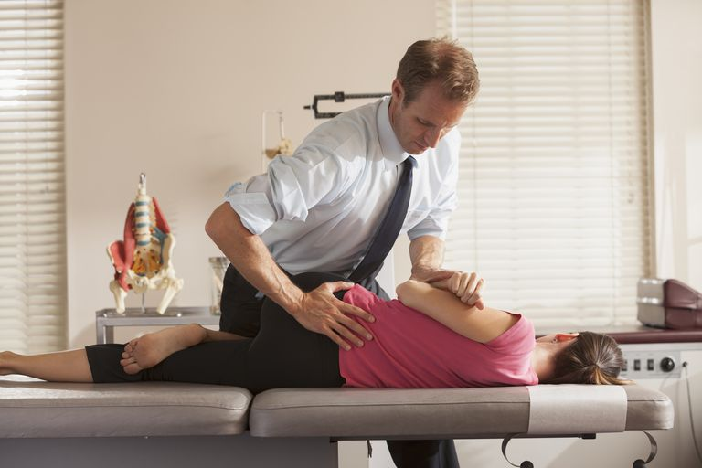 Woman lying on side getting adjusted by chiropractor