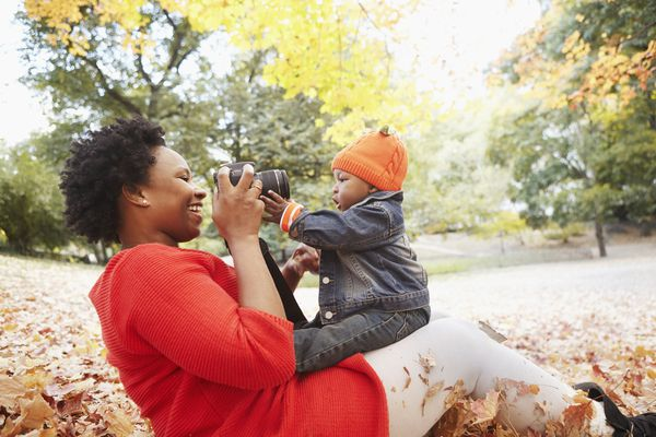 Mother taking pictures of toddler son in park