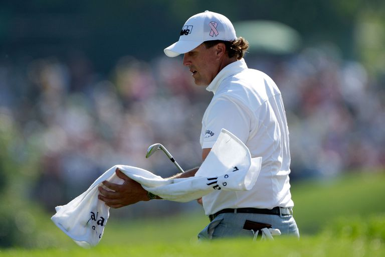 Phil Mickelson cleans off a golf club during a PGA Championship practice day