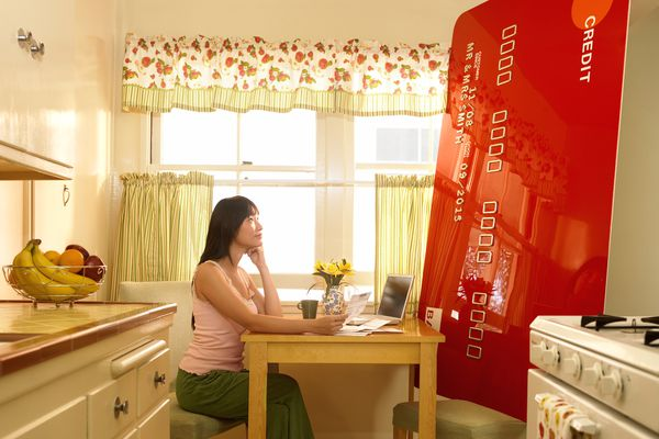 A woman sits across from a huge credit card