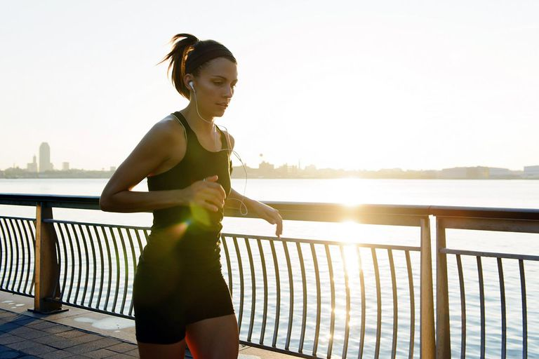 Young female jogger running at sunrise