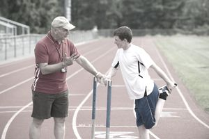 Coach helping high school track & field athlete
