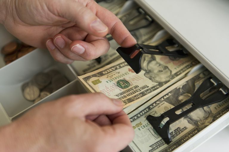 Close up of man's hand putting banknotes into cash register, studio shot
