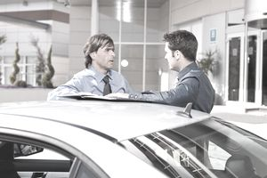 Businessmen talking near car