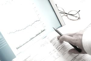 Woman looking at financial booklet, close-up of hand and graph