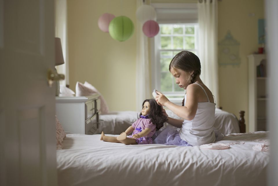 Caucasian girl brushing hair of doll on bed