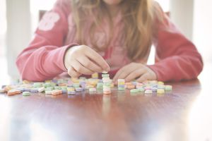 Caucasian girl stacking candy on table