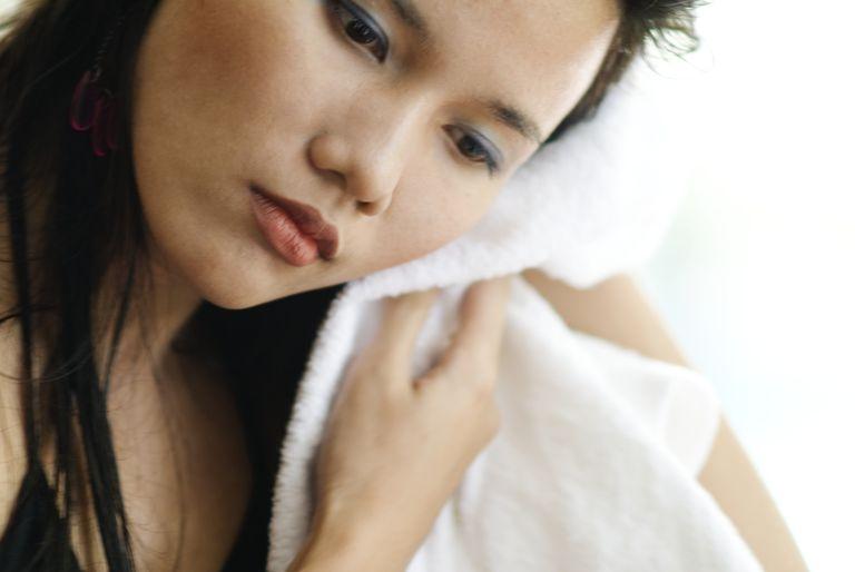 Thailand, Bangkok, Thai woman toweling face dry.