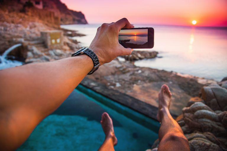 Taking mobile photo at sunset