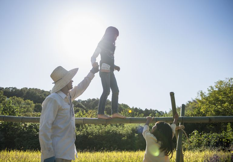 Man and two girls playing on horizontal bamboo