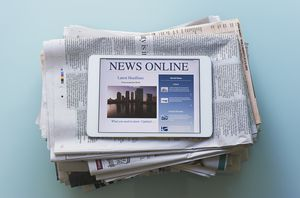 Stack of newspapers topped by a tablet showing online news.