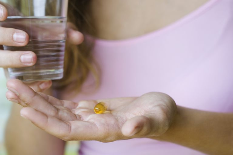 woman taking fish oil supplement