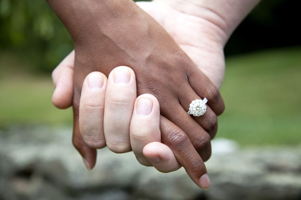 nterracial Couple Holding Hands and Diamond Engagement Ring