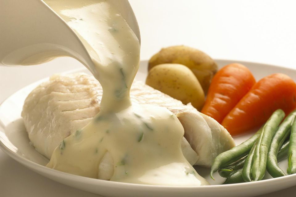 Parsley sauce poured over cod and vegetables