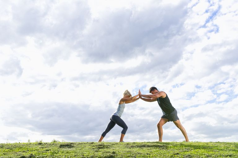 A man and woman using training in a field using isometrics.