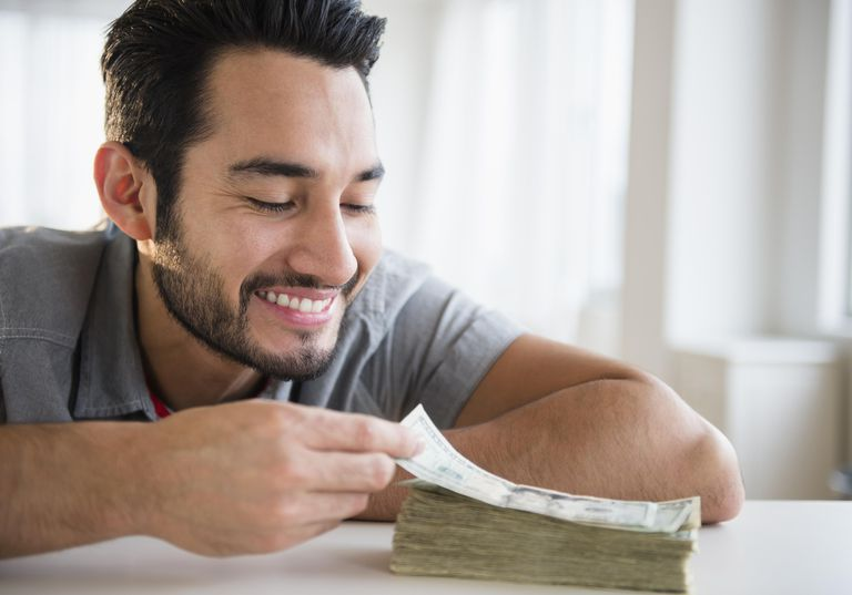 Mixed race man counting stack of money