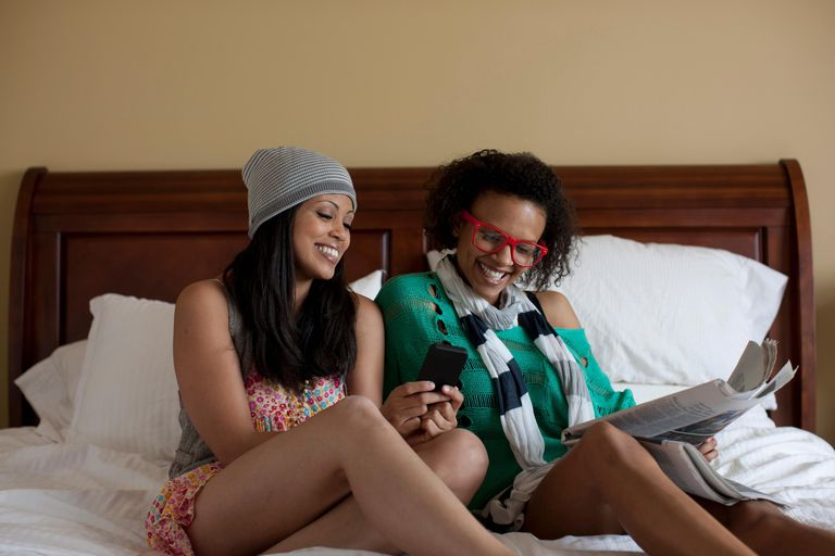 Young women sitting on bed using mobile phone, laughing