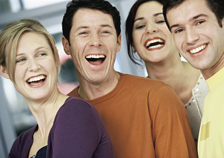 Four people smiling and choosing to be happy at work.