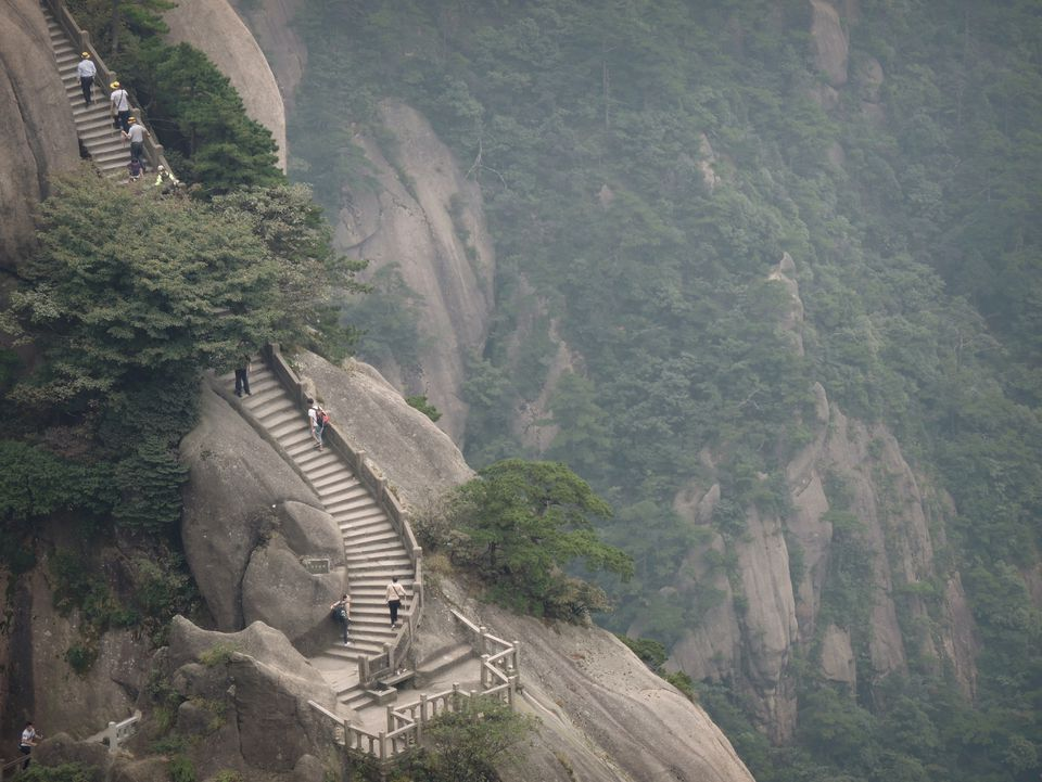 Mountain edge hiking along Huangshan / Yellow mountain stairs by canyon cliff, China