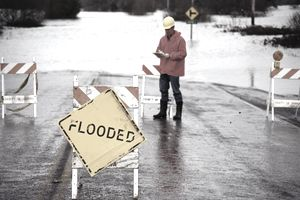 """Man in orange jacket standing next to flooded area near """"flooded"""" sign"""