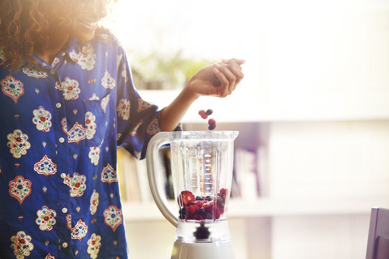 Woman dropping berries into a blender