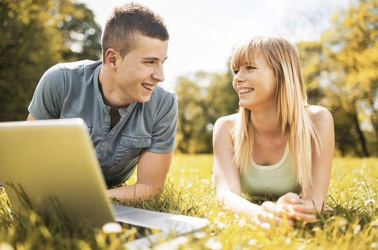 Teenage couple using laptop outdoors.