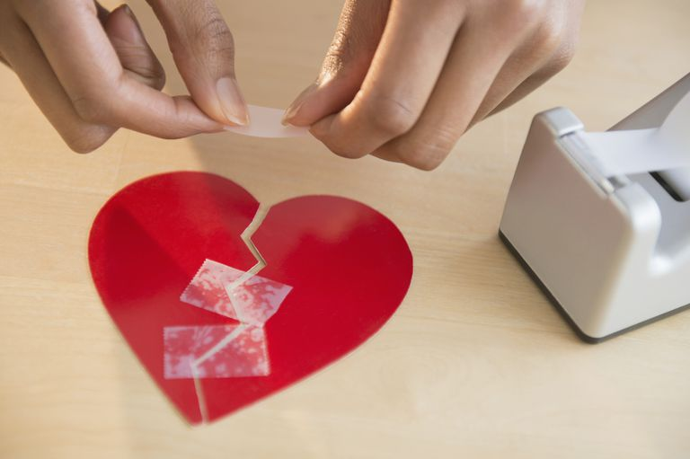 Person taping together havles of a broken paper heart