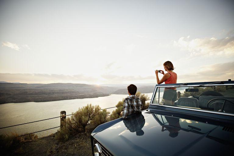 Couple watching desert sunset woman taking photo