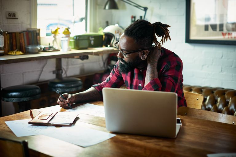 Male designer with tattoos drawing at desk.
