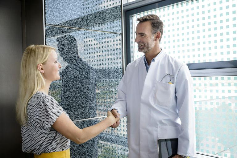 Senior doctor shaking patient`s hand, smiling