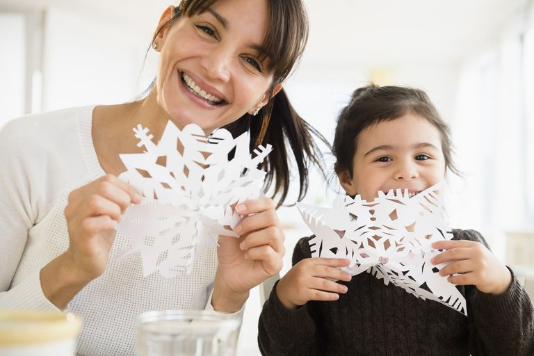 Hispanic mother and daughter making paper snowflakes