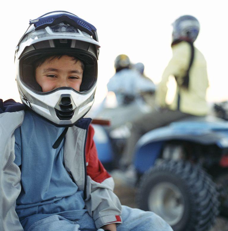 Boy (4-6) sitting on ATV, family in background