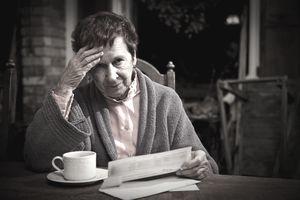 unhappy elderly woman looking at bills.