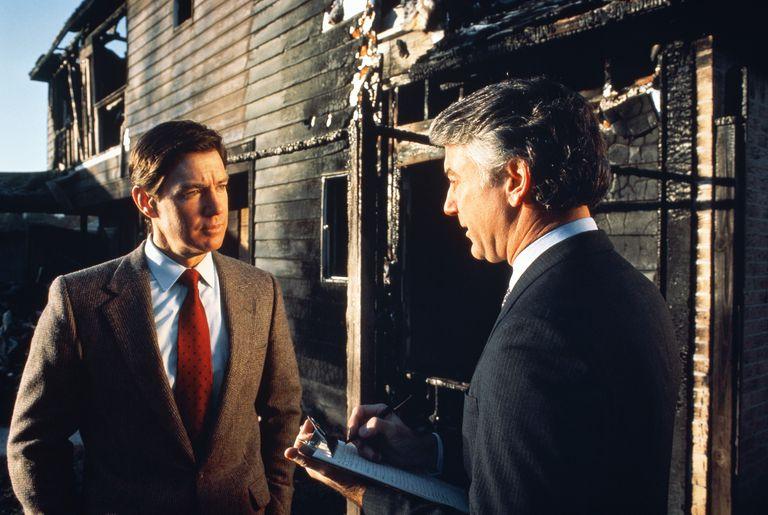 Two men talking outside a fire-damaged building