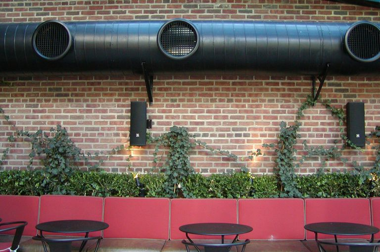 black industrial venting on top of brick wall with planter and tables and chairs