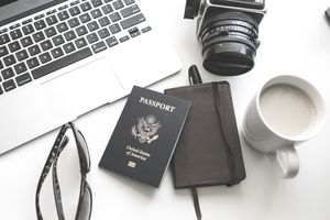 Preparing to travel, with passport, camera, and notes