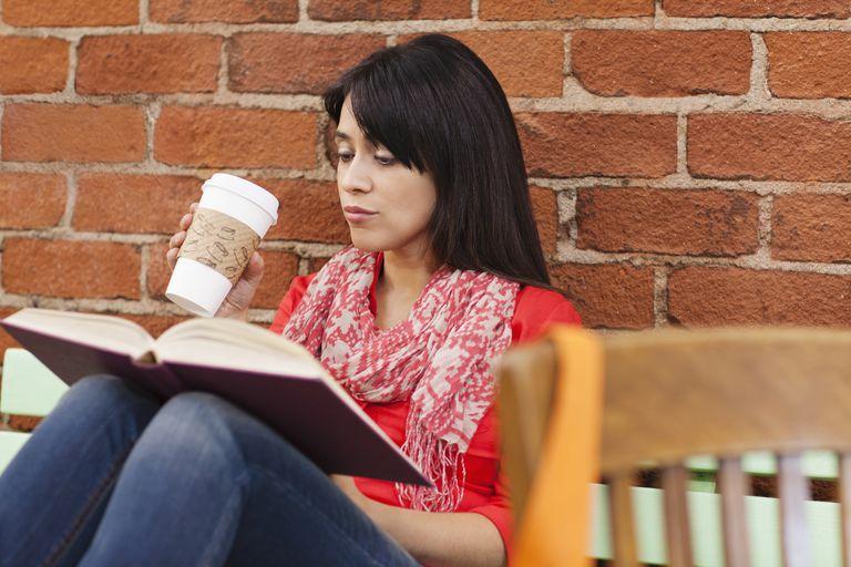 Mujer leyendo un libro y tomando café