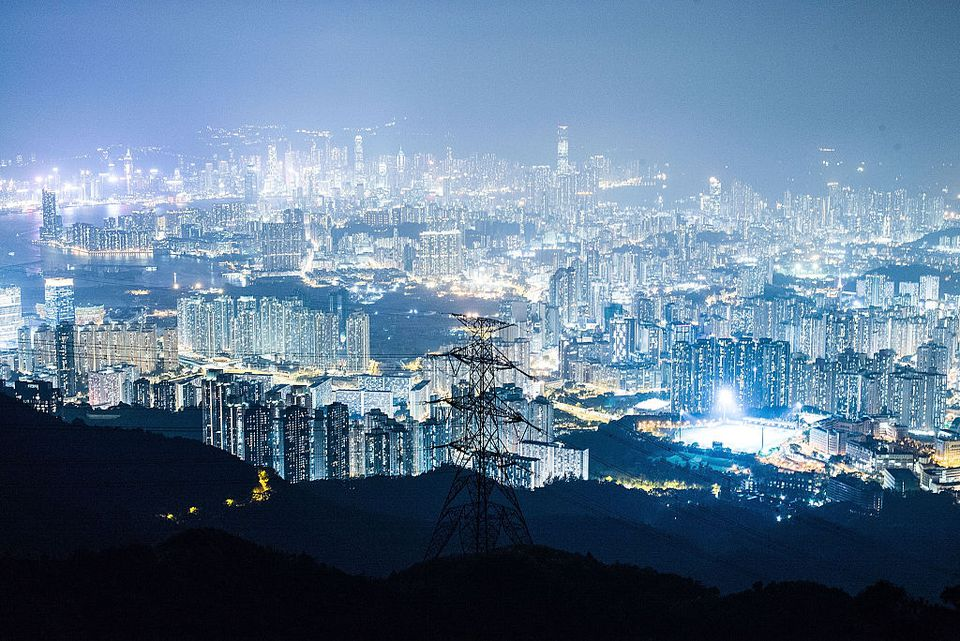 The view from Kowloon Peak shown apartment buildings and office blocks lights at night.
