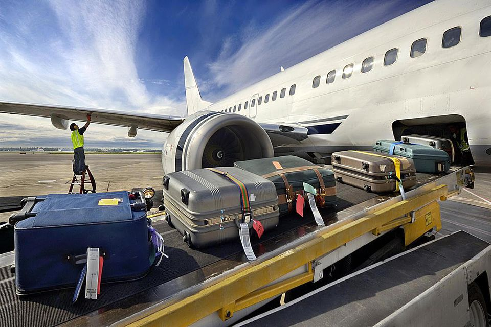 Worker checking wing as luggage rolls onto airplane