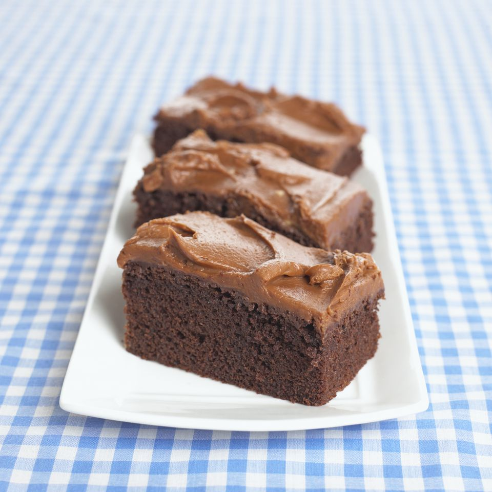 Three slices of chocolate cake on white platter on blue and white checked tablecloth, close-up