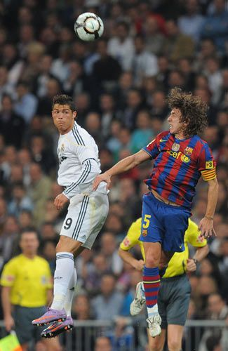 Cristiano Ronaldo of Real Madrid goes for a high ball against Carles Puyol of Barcelona
