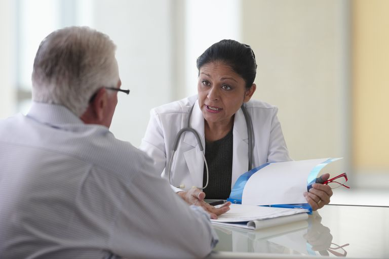 Female doctor consulting with male patient